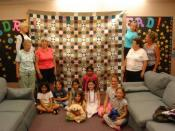 Quilt hanging vertically, young children sitting on floor at base, ladies standing on either side, some looking at quilt