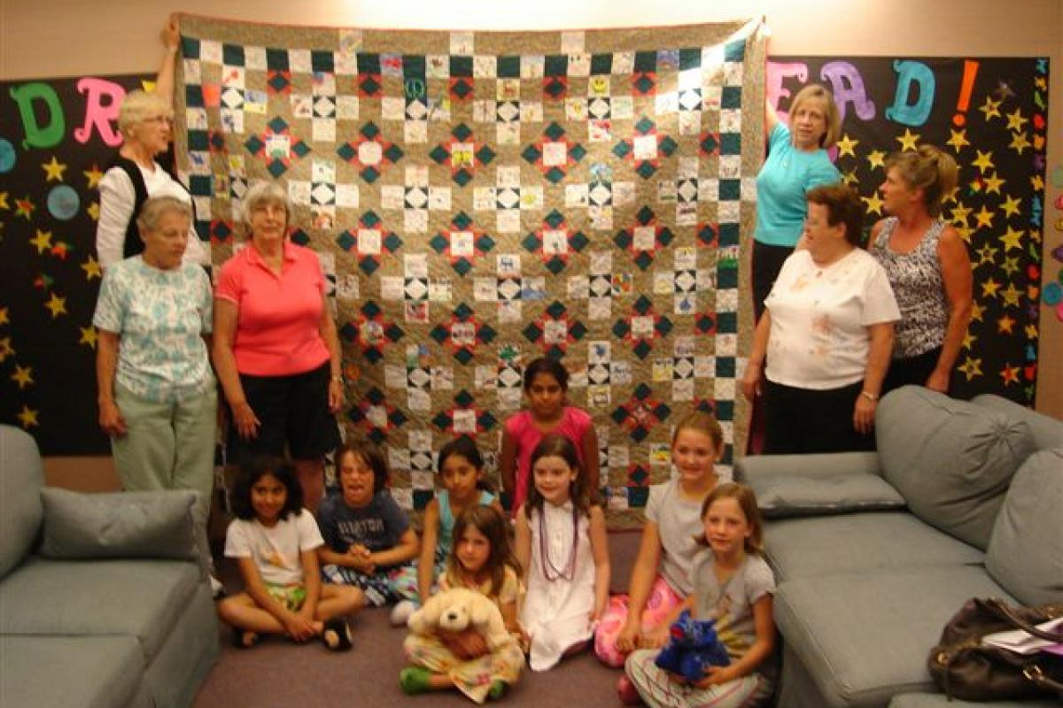 Needles & Things and Gunn-Quilt hanging vertically,children on floor in front, women standing at sides, one looking at the quilt